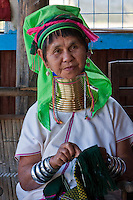 Myanmar, Burma.  Padaung Woman with Brass Neck Coils, Sewing.  Inle Lake, Shan State.  The Padaung are also called Kayan Lahwi.