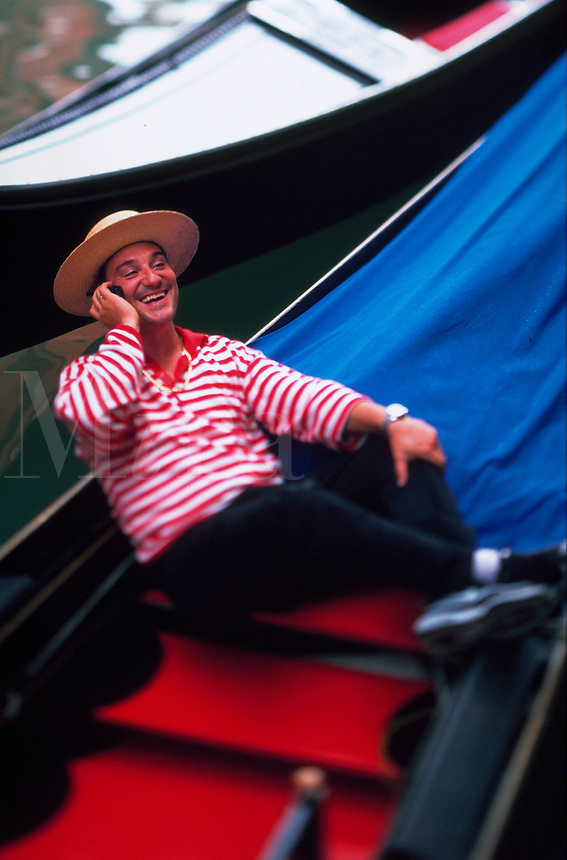 Gondolier sitting in his gondola and talking on his cell phone in Venice, Italy.