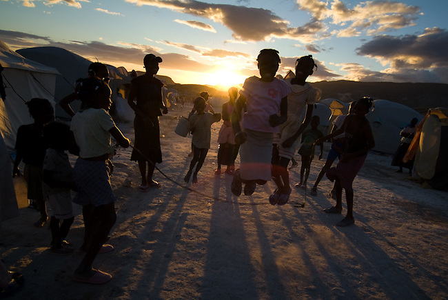 """Jeans sisters and neighbours playing with a skkiping rope in the sunset in the sheltercamp """"Hanna de Praville"""" in Gonaives."""