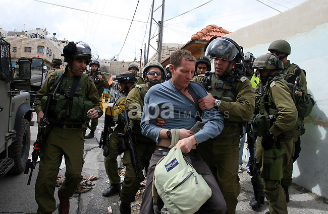 Israeli troops arrest a protester during a demonstration by Palestinians and peace activists demanding the reopening of a key street in the West Bank city of Hebron, 24 February 2012. Hundreds of Palestinians protested to demand the city's main Shuhada Street be reopened after an 18-year closure by the Israeli military on security grounds. Photo by Issam Rimawi