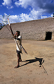 Koatinemo village, Brazil. Assurini Indian man demonstrating his bow and arrow skills outside the House of the Dead. Para State.
