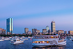 Boats gather on the Charles River at dusk before the July 4th fireworks in Boston, Massachusetts, USA