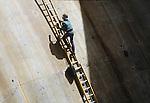 Construction worker on ladder repairing dam.