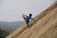 Child scales a large sand mound as he works collecting stone. At least 10,000 people, including 2,500 women and over 1,000 children, are engaged in stone and sand collection from the Bhollar Ghat on the banks of the Piyain river. Building materials such as stone and sand, and the cement which is made from it, are in short supply in Bangladesh, and commands a high price from building contractors. The average income is around 150 taka (less than 2 USD) a day...