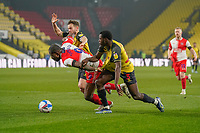 Uche Ikpeazu of Wycombe Wanderers (centre) is tackled by Jeremy Ngakia of Watford during the Sky Bet Championship behind closed doors match between Watford and Wycombe Wanderers at Vicarage Road, Watford, England on 3 March 2021. Photo by David Horn.