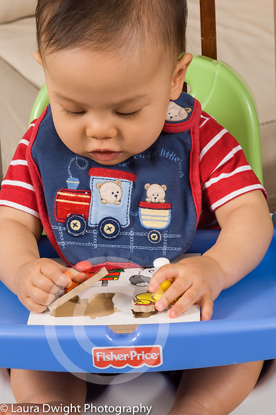 9 month old baby sitting in infant seat using pincer grasp to pick up peg puzzle piece