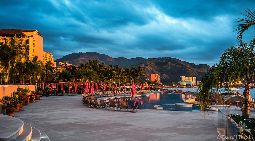 Fine Art Landscape Photograph Scenic of the Grand Venitian pool. A sunset photograph set amongst the ocean and mountains in Puerto Vallarta, Mexico.