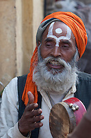 Pashupatinath, Nepal.  Sadhu (Holy Man) at Nepal's Holiest Hindu Temple, Playing a Drum.  The trident on his forehead marks him as a devotee of Shiva.