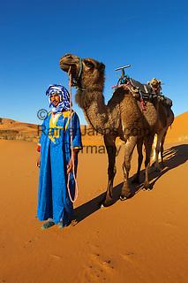 Morocco, Meknes-Tafilalet, Merzouga: Erg Chebbi, large dunes formed by wind-blown sand, with Moroccan man in traditional dress and camel | Marokko, Meknes-Tafilalet, Merzouga: Erg Chebbi, durch Verwehungen entstandene Duenen, und Einheimischer in traditioneller Kleidung mit Kamel
