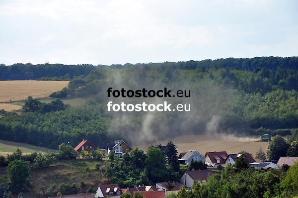 """Mähdrescher bei der Ernte auf einem Feld am Ortsrand von Offenheim wirbelt viel """"Staub"""" auf"""