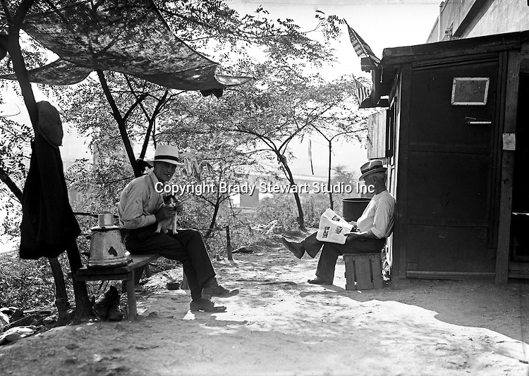 Pittsburgh PA: Two men and a cat passing the time.  The 17th Street Bridge is in the background. During the depression, the area from the PA RR Station to the 17th street bridge was called Shantytown.  Father Cox, a local priest, helped the residents through food kitchens and highlighting their plight.  Brady Stewart photographed the area for the City of Pittsburgh.