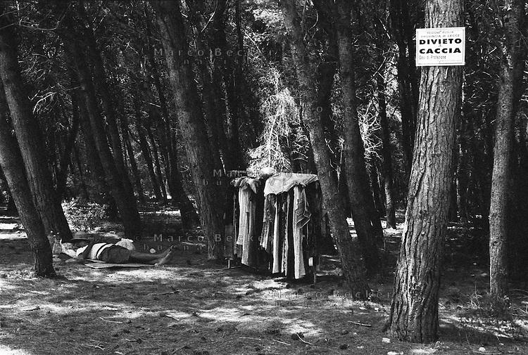 S. Andrea frazione di Melendugno (Lecce). Un venditore ambulante di abiti fa la siesta all'ombra della pineta in un'Oasi di protezione faunistica vicino al mare --- S. Andrea frazione di Melendugno (Lecce). A peddler of clothing  has a siesta in the shade of a pine forest in a Oasis of fauna protection near the sea