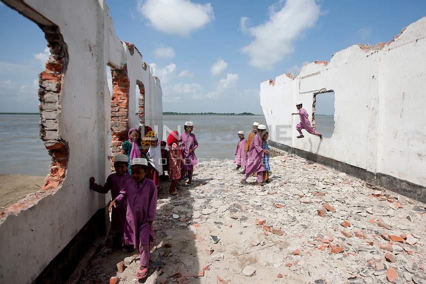 Every year in Bangladesh, millions of people are affected by river erosion that destroys home, farmland, communication infrastructure. In the last couple of days erosion by the Padma River has caused extensive damages to houses, agricultural lands, roads etc. In Dohar, lots of people lost their lands and homes due to Padma river banks erosion. Dohar, Dhaka, Bangladesh.