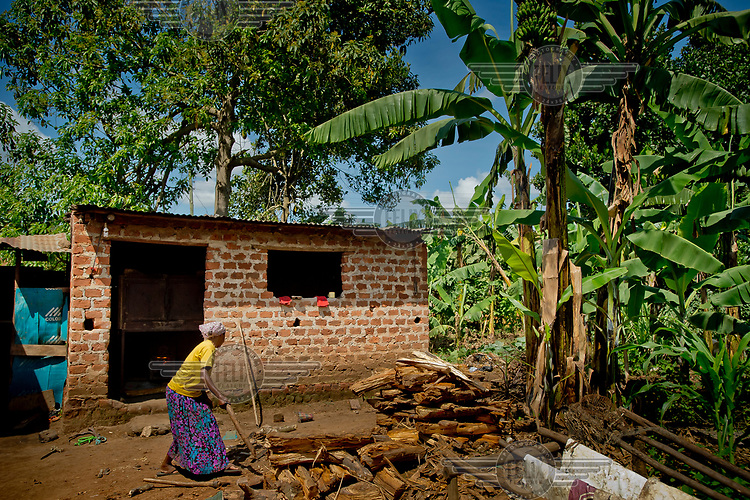 In the Kawempe district of Kampala, a woman belonging to the Frontier Orphanage and Elderly Home (FOEH) group cuts firewood in front of the brick shed in which an economical combustion oven is installed. The oven uses a small amount of wood to produce maximum cooking capacity, allowing significant savings. Thanks to the acquisition of the oven, FOEH undertook a bakery business to generate income improving the lives of its members.