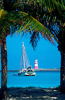 Fishing boat and lighthouse framed by palm trees. Nassau, Bahamas.