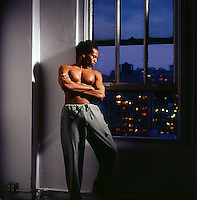 Shirtless African American man leaning against wall looking out window at night<br />