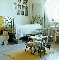 A girl's bedroom with a wrought-iron bed and little table and chairs with gingham cushions