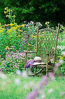 Her Garden and hat-- purple and yellow flowers surround a handwoven rocking chair