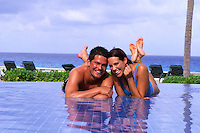 Fun Hispanic couple in shallow pool on the beaches of Cancun Mexico.