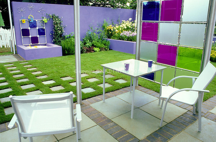 Color theme garden backyard landscaping, lavender and purple with green, blues, flagstone and brick mixed materials patio, furniture, privacy screen, purple wall, children's sandbox play area with cover, lush flower garden in raised bed, lawn grass grid with stone walkway path, view, great outdoor living for family