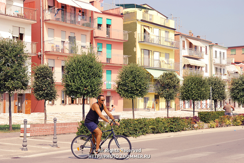 Man riding a bike in Italian resort town Sottomarina (Chioggia) on a street with typical Italian houses