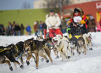 Mitch Seavey's team rounds the corner at Cordova street during the 2016 Iditarod Ceremonial Start in downtown Anchorage. Photo by James R. Evans