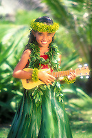Young Hawaiian girl (age 7) playing ukulele wearing ti leaf skirt and maile leis with a haku lei on her head