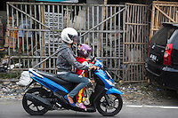 Yogyakarta, Java, Indonesia.  Road Safety.  Mother and Little Girl on Motorbike, with Helmets.