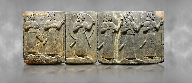 Hittite relief sculpted orthostat stone panel of Royal Buttress Basalt, Karkamıs, (Kargamıs), Carchemish (Karkemish), 900-700 B.C. Warriors. Anatolian Civilisations Museum, Ankara, Turkey.<br /> <br /> Right panel - Three figures each with a long dress, a thick belt and curly hair. The figure in front holds a spear with a broken tip in his left hand and a leafy branch in his right hand. The figure in the middle made his left hand a fist, and he carries a tool with his right hand at the level of his head. They are followed with a figure holding a sceptre in his left hand. All three have each a long sword at their waist. <br /> <br /> Against a grey art background.