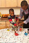 4 year old boy in kitchen with father learning how to open can with can opener, hleping him cook