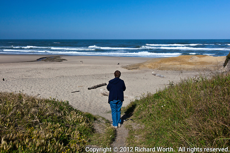 A lone visitor to Pomponio State Beach surveys a distant horizon under a cloudless sky while waves gently roll to shore on the California coast near San Francisco.
