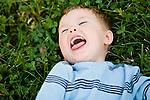 USA, Illinois, Washington, Boy (2-3) lying on grass and laughing