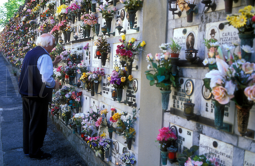 Italy, Fiesole, elderly man placing flowers in cemetery