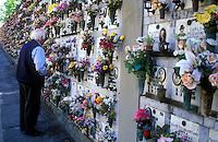 Italy, Fiesole, elderly man placing flowers in cemetery