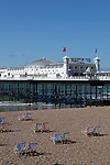 Great Britain, England, East Sussex, Brighton: Deck chairs on pebble beach with Brighton Pier behind