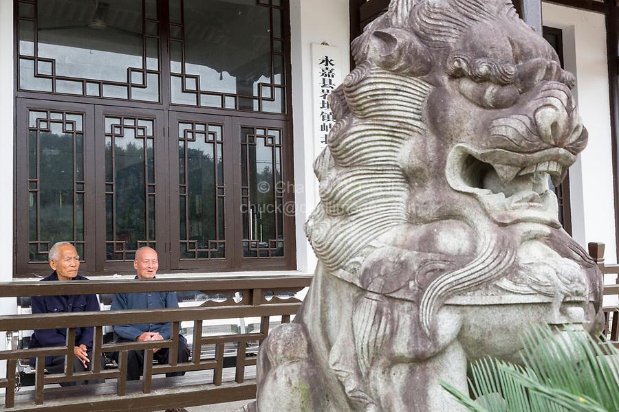Yubei, Zhejiang, China.  Two Elderly Gentlemen on Porch, with Guardian Lion (Shi, or Foo Dog) in Foreground.