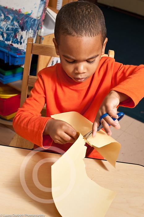 Education preschool 3-4 year olds boy cutting paper with scissors