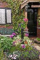 """Front entrance of old house with black picket fence, old pump, black door, patio, flower garden, vines, trees, dogwood, honeysuckle, house name sign of """"The Cottage"""", trug of herb plants for inviting welcome, curb appeal entry"""