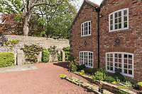 BNPS.co.uk (01202) 558833. <br /> Pic: SandersonYoung/BNPS<br /> <br /> Driveway.<br /> <br /> A quirky 'show home' for a brickwork owner where Lewis Carroll is believed to have stayed while writing some of his Alice in Wonderland books is on the market for just under £1m.<br /> <br /> Red Cottage is a striking Grade II listed property in Whitburn, Tyne and Wear, where Charles Dodgson, otherwise known as Lewis Carroll, regularly visited family.<br /> <br /> The unusual 179-year-old home was built to show off as many design features as possible, and has a walled garden and even an air raid shelter.