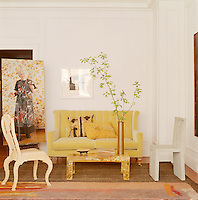 In the living room a large photograph by Anna-Maija Aaras has been arranged next to a yellow Arts & Crafts sofa with chairs by Julian Major, Peter Woolin and Kate Staddon on either side of a French coffee table dating from the 1960's