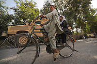 two Afghan children bicycle past an  RG31 MRAP vehicles from RCP29 (103rd Mountain Division - Route Clearance Patrol),  outside a police compound  in the Kunar Valley near the Pakistan border.