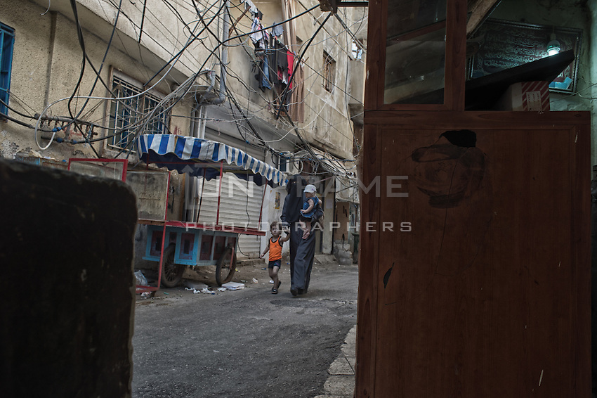 Woman carrying her children in the streets of the Shatila camp. Beirut, Lebanon. August 2015