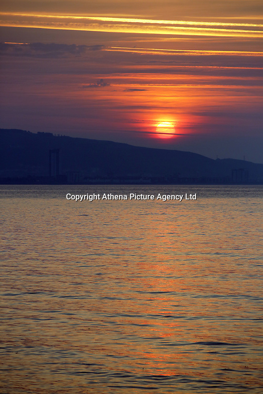 Pictured: The sun rises over Kilvey Hill in Swansea, as seen from West Cross in south Wales, UK. Wednesday 21 June 2017<br />Re: Summer Solstice