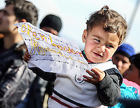 "Pictured: A young boy holding a piece of paper with a ""Open borders Macedonia""  slogan Thursday 03 March 2016<br /> Re: Migrants have closed off the railway track at the Greek Fyro Macedonian border in Idomeni, Greece,"