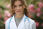 Portrait of a young woman, medical practitioner, healthcare professional, doctor, physician wearing a lab coat in natural outdoor settings with blossoming flowers behind