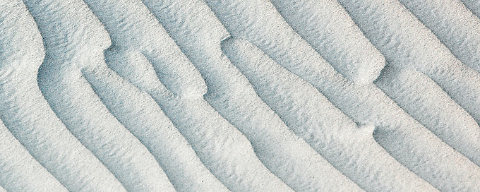 Soft evening light highlights the textures of Death Valley's many sand dunes, photographed with a telephoto lens.