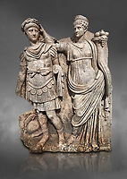 Roman Sebasteion relief  sculpture of Nero being crowned emperor by Agrippina, Aphrodisias Museum, Aphrodisias, Turkey.  Against a grey background.<br /> <br /> Agrippina crowns her young son Nero with a laurel wreath. She carries a cornucopia, a symbol of Fortune and Plenty, and he wears the armour and cloak of a Roman commander, with a helmet on the ground near his feet. The scene refers to Nero's accession as emperor in AD 54, and belongs before AD 59 when Nero had Agrippina murdered.