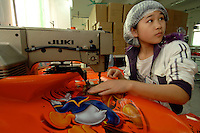 Worker makes a Disney carrier bag at the Richall factory in Donguan, Guangdong province, China. The plastic bags can be used many times and are seen as environmentally friendly. The company makes plastic bags for several clients including Disney and Sainsbury's...