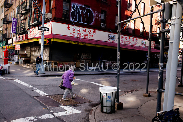 """New York, New York<br /> April 4, 2020<br /> <br /> China Town in lower Manhattan.<br /> <br /> The coronavirus has transformed urban architectural spaces with fear of proximity. Not entirely void of humanity, social distancing, within expansive city environments has created a landscape of aggrandizing physical structures and expanding spaces while diminishing the scale of humans. Face masks enhance the anonymity of """"the person"""", reducing them to a figure or an uninterrupted shadow falling on a surface."""