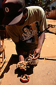 The Gambia. Market trader selling kola nuts from a glass jar; Boss hat, rasta t-shirt.